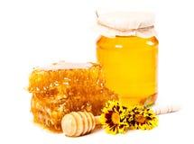Panal y tarro dulces de miel con el palillo y las flores Foto de archivo libre de regalías