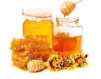 Panal y tarros de miel con el palillo y las flores aislados en w Foto de archivo