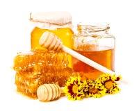 Panal y tarros dulces de miel con el palillo y las flores Imagenes de archivo