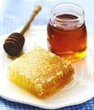 Panales con la miel, la miel en el tarro de cristal y el cazo de madera de la miel Foto de archivo