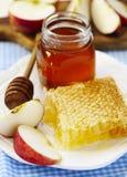 Panales con la miel, la miel en el tarro de cristal y las rebanadas de manzana en la placa Foto de archivo libre de regalías