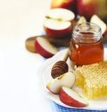 Panales con la miel, la miel en el tarro de cristal y las rebanadas de manzana en la placa Imagen de archivo libre de regalías