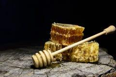 Panales y palillo a la miel en fondo de madera Imagen de archivo libre de regalías