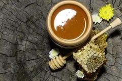 Panales y palillo a la miel en fondo de madera Fotos de archivo