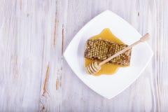 Panales y palillo para la miel en el fondo de madera blanco Foto de archivo libre de regalías