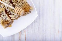 Panales y palillo para la miel en el fondo de madera blanco Fotos de archivo