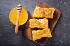 Panales y tarro de miel en fondo oscuro fotografía de archivo