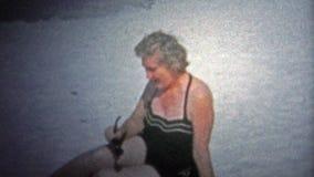 PANAMÁ CITY, ETATS-UNIS - 1959 : Femme utilisant un maillot de bain de concepteur à la plage des vacances banque de vidéos