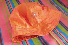Panama on beach mat. Woman orange panama on striped beach mat Royalty Free Stock Photo