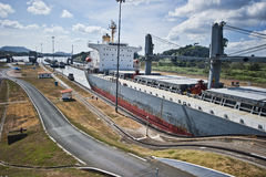 Panama canal. A cargo ship transiting through Panama canal on a sunny day. The transit is assisted by 4 locomotives on rails Stock Photos
