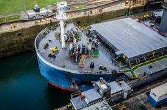 Electric locomotives pull ships in transit through the locks the Panama Canal. Panama Canal, Panama - February 20, 2015: Ship in Miraflores Locks Panama Canal Royalty Free Stock Image