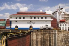 Panama Canal With Ship. One of the main buildings at Gatun Locks in the Panama Canal with a large container ship full of cargo in the background stock images