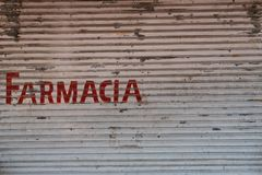 Farmacia pharmacy written on closed shutter storefront in Pa