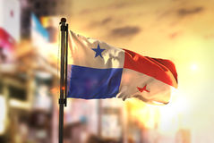Panama flaga Przeciw miasta Zamazanemu tłu Przy wschodu słońca Backlight Fotografia Stock