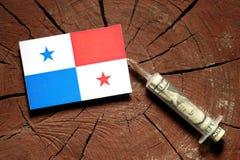 Panama flagga på en stubbe med injektionssprutan som injicerar pengar Royaltyfria Foton