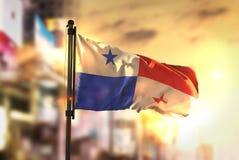 Panama-Flagge gegen Stadt unscharfen Hintergrund an der Sonnenaufgang-Hintergrundbeleuchtung Stockfotografie