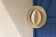 Panama hat on blue door. Panama hat hanging from blue wooden door Stock Photos