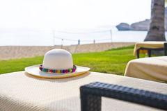 A Panama hat with colorful brim. A Panama hat with colorful decoration on a chair next to the beach stock images