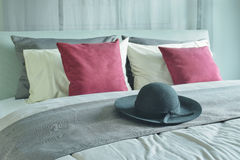Panama hat setting on bed runner with pillows in deep red, white and gray colors stock images