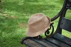 Panama hat on wooden chair with green grass field background Royalty Free Stock Photos