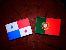 Panamaische Flagge mit portugiesischer Flagge auf einem Baumstumpf lokalisiert lizenzfreies stockbild