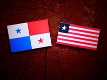 Panamanian flag with Liberian flag on a tree stump isolated. Panamanian flag with Liberian flag on a tree stump Stock Photos