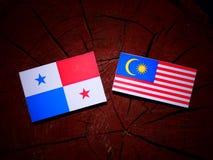 Panamanian flag with Malaysian flag on a tree stump isolated Stock Photos