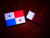 Panamanian flag with Qatari flag on a tree stump isolated. Panamanian flag with Qatari flag on a tree stump Royalty Free Stock Image