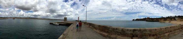 Panaromic sikt av däcket som går till pir med havet & möte för molnig himmel i horisont royaltyfria bilder