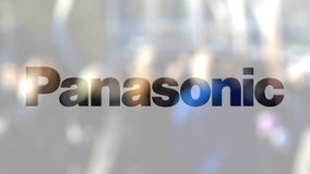 Panasonic Corporation logo on a glass against blurred crowd on the steet. Editorial 3D rendering. Panasonic Corporation logo on a glass against blurred crowd on stock video footage
