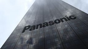 Panasonic Corporation logo on a skyscraper facade reflecting clouds, time lapse. Editorial 3D rendering. Panasonic Corporation logo on a skyscraper facade stock footage