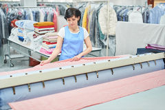 Pancadinhas do trabalhador da lavanderia da mulher o linho na máquina automática imagens de stock royalty free