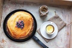Pancake, bacche, inceppamento e tè su un vassoio di legno Immagini Stock
