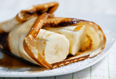 Pancake with banana and maple syrup Stock Photos