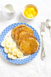 Pancake and banana slices on a blue plate on a bright surface. Delicious and healthy breakfast. Stock Photos