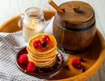 Pancake with berries on wooden tray. A barrel of honey Royalty Free Stock Photography