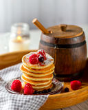 Pancake with berries on wooden tray. A barrel of honey Stock Photography