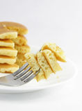 Pancake Bite. Close up of a bite of pancake in a fork ready for eating with the background of a stack of pancakes Royalty Free Stock Image