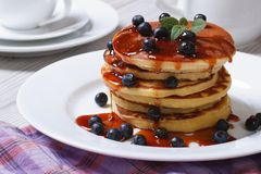 Pancake with blueberries and maple syrup on a white plate Royalty Free Stock Image