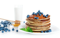 Pancake with blueberries, mint, milk and honey on a white backgr Stock Photos