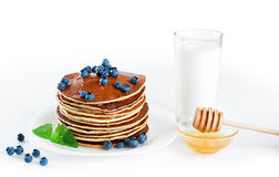 Pancake with blueberries, mint, milk and honey on a white backgr Stock Photo