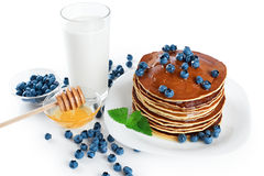 Pancake with blueberries, mint, milk and honey on a white backgr Stock Image