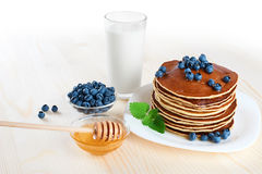 Pancake with blueberries, mint, milk and honey on a white backgr Royalty Free Stock Images