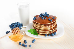Pancake with blueberries, mint, milk and honey on a white backgr Royalty Free Stock Photography