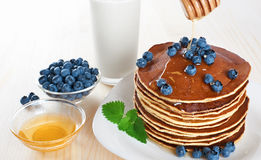 Pancake with blueberries, mint, milk and honey on a white backgr Royalty Free Stock Image