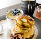 Pancake breakfast. A pancake breakfast with syrup, bacon, coffee and juice Royalty Free Stock Photos