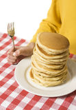 Pancake Breakfast 2. Giant plate of pancakes, with a hand holding a fork against a red checkered tablecloth Royalty Free Stock Photos