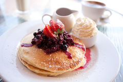 Pancake breakfast. Pancake stack with berries, fresh cream and maple syrup Stock Photography
