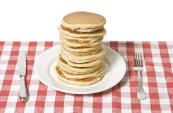 Pancake Breakfast. Giant plate of pancakes, a knife and fork on a table cloth Royalty Free Stock Photography