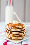 Pancake with butter and honey, a bottle of milk, dessert Stock Image
